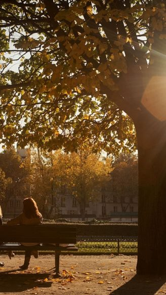 Two women sitting on park bench in afternoon at Paris, France.