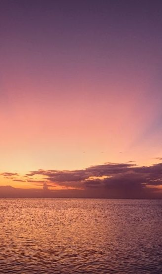 Beautiful sunrays in pink and blue against orange colors at sunset at Fort Myers Beach, Florida in October.