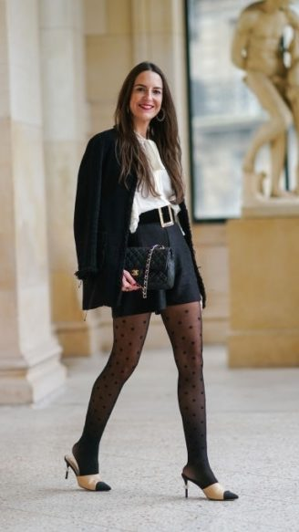 PARIS, FRANCE - JANUARY 12: Alba Garavito Torre wears a black jacket from Zara, a white ruffle shirt from Zara, a black large belt,  black shorts from Pain de Sucre, Chanel logo printed tights, pointy shoes from Chanel with high heels and pearl details, a black leather quilted bag from Chanel, on January 12, 2021 in Paris, France. (Photo by Edward Berthelot/Getty Images)
