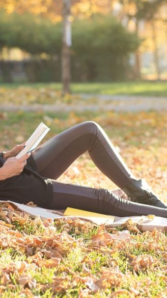 Carefree young woman reading a book and relaxing in the park.