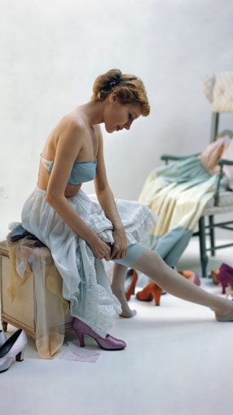 Model putting on her stockings, wearing a strapless blue wired brassiere with a white petticoat by Iris and light pink lipstick. (Photo byJohn Rawlings/Condé Nast via Getty Images)