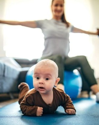 Two people, baby playing on the floor while his mom is exercising at home