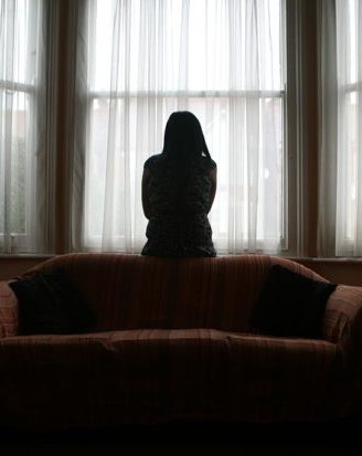 A young Asian woman suffering from domestic violence stands alone in the bay window of her home. (Photo by In Pictures Ltd./Corbis via Getty Images)