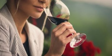 Closeup of unrecognizable adult woman holding a glass of red wine and smelling it before tasting. She's standing outdoors on summer afternoon. Blurry gras and red flowers in background. Toned image.