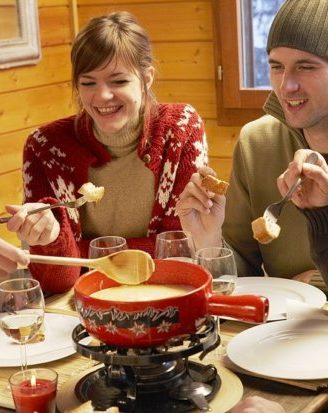 group of young people eating fondue in a chalet