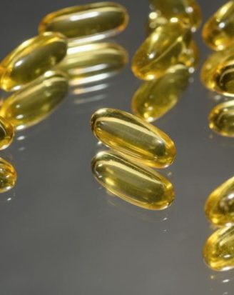 Omega 3 capsules close-up on a hard-light mirror