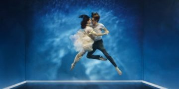 A couple dancing under water in a intimate moment