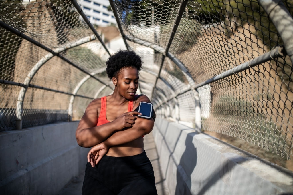 Healthy woman touching phone screen on armband before exercising outdoors. African american woman in sports clothing using phone while exercising outdoors.