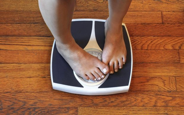 A woman on a bathroom scale hides the numbers with her foot because she is unhappy with her weight.